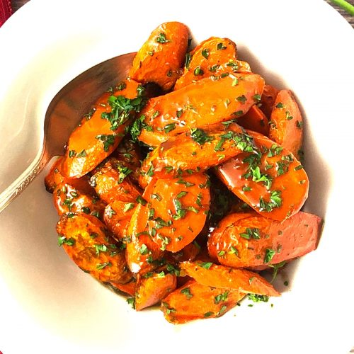 close up top shot of air fryer roasted carrots with brown sugar butter glaze and parsley