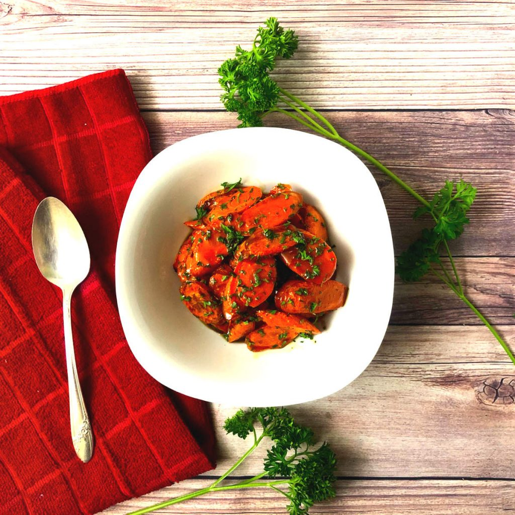 Top shot of air fried carrots with parsley and sweet butter sauce with roasted air fryer garlic