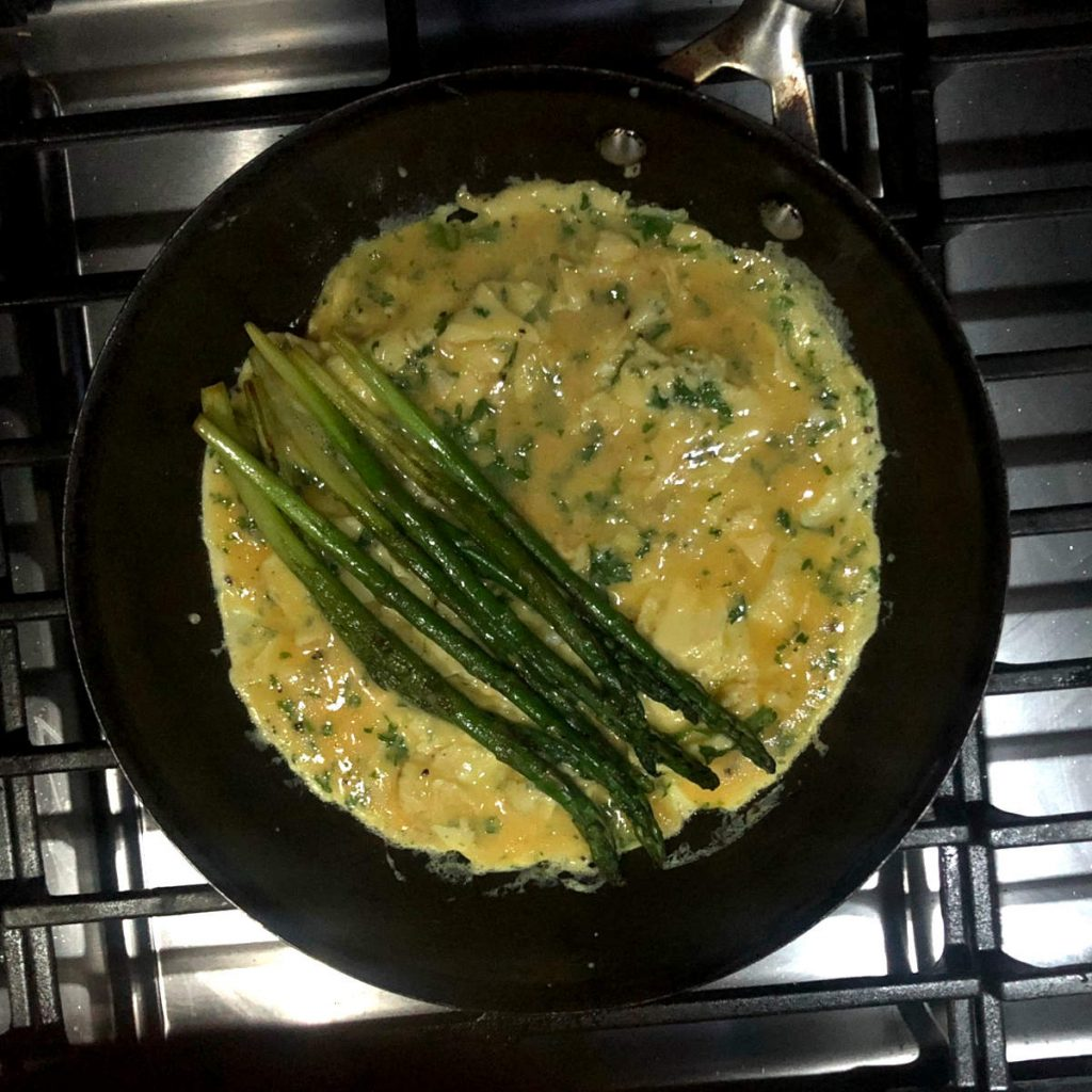 cooking omelette with asparagus and parsley