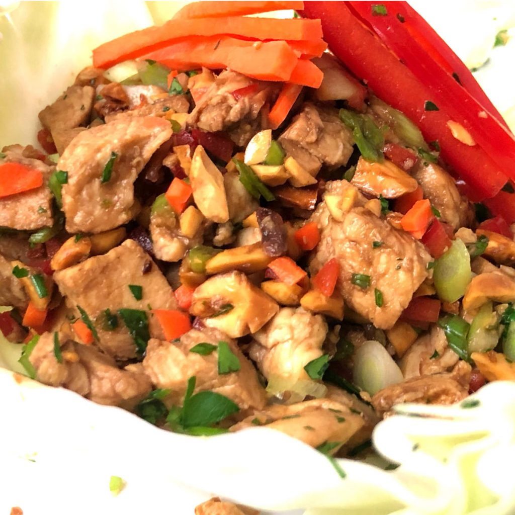 close up view of asian chicken cabbage wrap showing peanuts, chicken, and veggies, and julienne carrots and red bell peppers