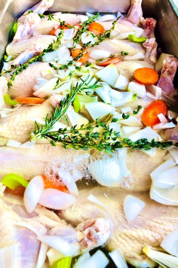 mary's chicken poached in white wine with garlic, herbs, and mirepoix base
