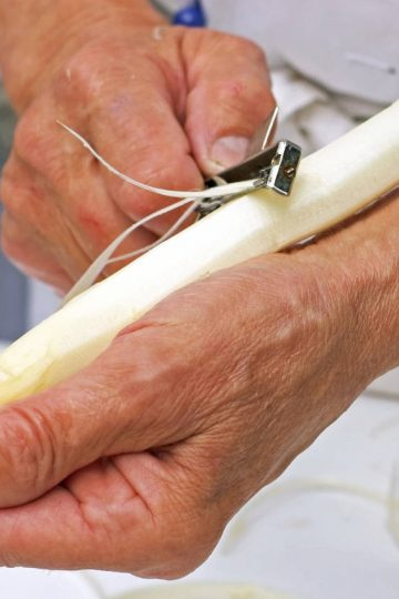Demonstrating how to peel asparagus correctly using a thick white stalk of asparagus