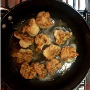 frying golden brown cauliflower in pan on stove