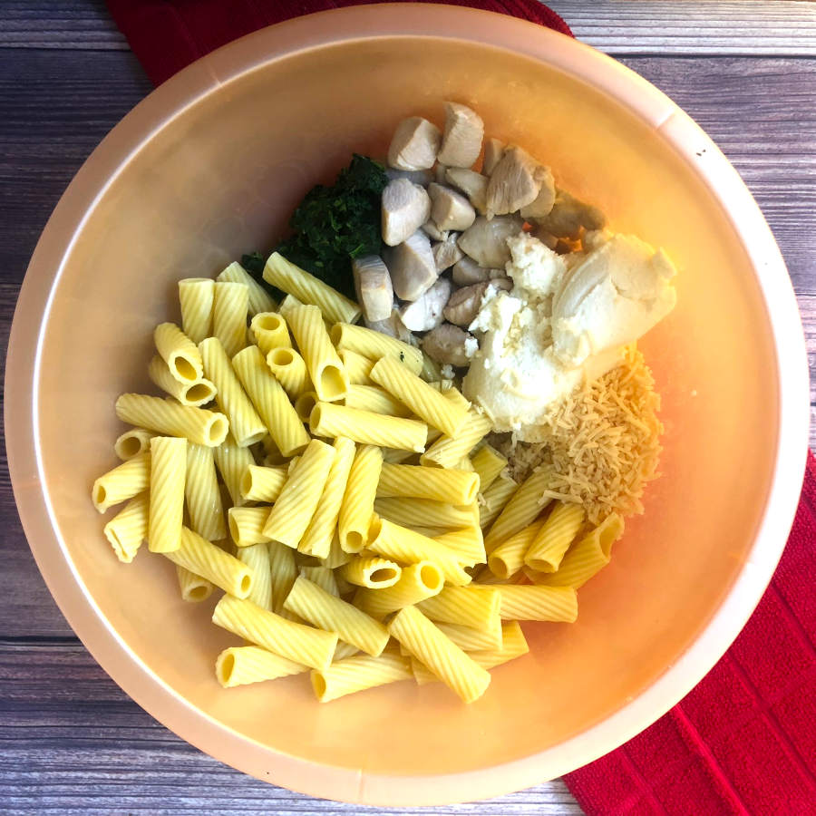 mixing rigatoni with ingredients for chicken baked ziti